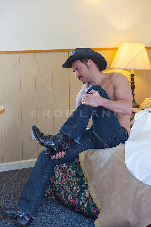 shirtless cowboy in a cheap motel room taking off his cowboy boots while seated on the edge of a bed