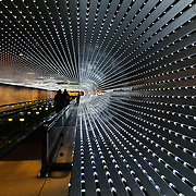 A walkway connecting the East and West buildings of the National Gallery of Art. The thousands of individual lights are programmed to move in a display as the pedestrians move along the walkway.