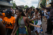 Girls dancing behind a sound system on Monday 28th August 2016 at the 50th Notting Hill Carnival in West London. A celebration of West Indian / Caribbean culture and Europes largest street party, festival and parade. Revellers come in their hundreds of thousands to have fun, dance, drink and let go in the brilliant atmosphere. It is led by members of the West Indian / Caribbean community, particularly the Trinidadian and Tobagonian British population, many of whom have lived in the area since the 1950s. The carnival has attracted up to 2 million people in the past and centres around a parade of floats, dancers and sound systems.