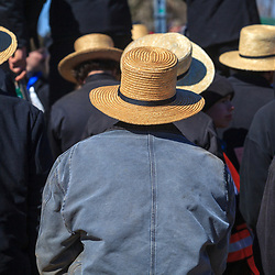 Gordonville, PA, USA - March 10, 2012: Amish farmers, wearing straw hats, watch an auctioneer sell farm equipment at a mud sale.
