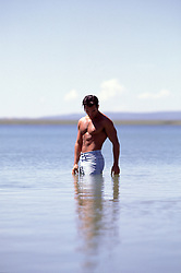 shirtless man in jeans standing in a calm lake