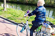 In Nieuwegein fietst een vrouw in de zon op een elektrische fiets met een windmolentje op het stuur.<br /> <br /> In Nieuwegein a woman is cycling on her e-bike in the sun with a small wind mill mounted at the steer.