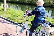 In Nieuwegein fietst een vrouw in de zon op een elektrische fiets met een windmolentje op het stuur.<br /> <br /> In Nieuwegein a woman is cycling on her e-bike in the sun with a small wind mill mounted at the steer.