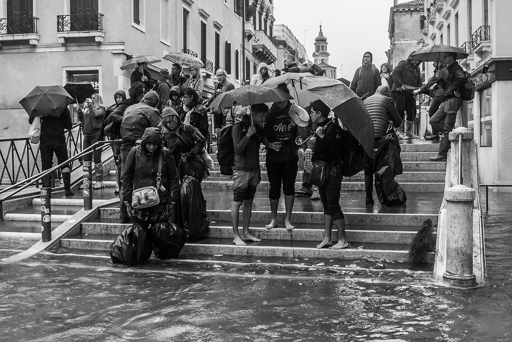 Venice, Italy. 29 October, 2018. People on a bridge walk through Strada Nova during the high tide on October 29, 2018, in Venice, Italy. This is a selection of pictures of different areas of Venice that the press has not covered, were resident live and every year they have to struggle with the high tide. Due to the exceptional level of the 'acqua alta' or 'High Tide' that reached 156 cm today, Venetian schools and hospitals were closed by the authorities, and citizens were advised against leaving their homes. This level of High Tide has been reached in 1979. © Simone Padovani / Awakening / Alamy Live News
