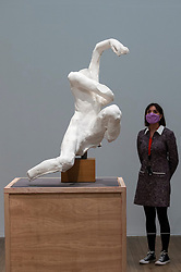 """© Licensed to London News Pictures. 11/05/2021. LONDON, UK. A staff member poses with """"Son of Ugolino, without head"""", 1904, by Auguste Rodin. Preview at Tate Modern of """"The Making of Rodin"""", a major new exhibition of over 200 sculpture works by Auguste Rodin, many of which have never been shown outside France. The exhibition marks the reopening of the museum as the UK government eases certain coronavirus lockdown restrictions and is open 18 May to 21 November.  Photo credit: Stephen Chung/LNP"""