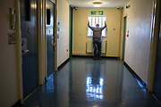 A prisoner staring out of a window down one of the corridors of the enhanced wing at <br /> HMP/YOI Portland, Dorset, United Kingdom.