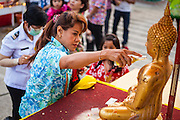 13 APRIL 2014 - BANGKOK, THAILAND: A woman bathes a Buddha statue in scented oils at Bangkok City Hall. Many people go to temples and religious ceremonies to make merit on Songkran. Songkran is celebrated in Thailand as the traditional New Year's Day from 13 to 16 April. Songkran is in the hottest time of the year in Thailand, at the end of the dry season and provides an excuse for people to cool off in friendly water fights that take place throughout the country. Songkran has been a national holiday since 1940, when Thailand moved the first day of the year to January 1.    PHOTO BY JACK KURTZ