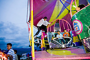 A ride attendant leaps from car to car as children swirl past on a carnival ride during the annual patron saint festival for Santiago Matamoros in Cuilapan, Oaxaca, Mexico on July 25, 2008.