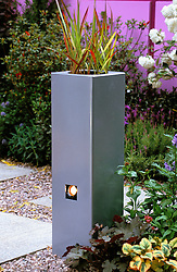 Galvanised steel planters with Imperata cylindrica and inset spotlight.<br /> 'Catwalk' garden, Chelsea 2003