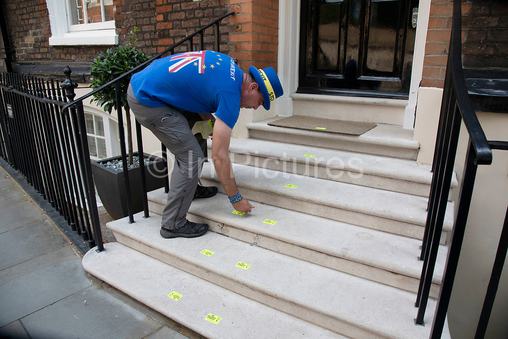 Anti Brexit protester Steve Bray placing anti-Brexit stickers outside a building in Westminster where Boris Johnson is taking part in a meeting on 16th July 2019 in London, England, United Kingdom.