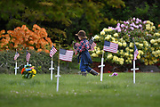 Jack Sayer helps prepare headstones for Memorial Day by distributing American flags onto every headstone belonging to a U.S. military veteran on May 24, 2019 at Bayview Cemetery in Ketchikan, Alaska.
