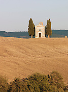 The iconic view of a small chapel atop a hill in Val D'Orcia in Tuscany, Italy