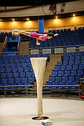 Cao Xiaoli, a professional acrobat, practices balancing on one hand in the practice room at Shanghai Circus World in Shanghai, China. (From the book What I Eat: Around the World in 80 Diets.) The caloric value of her day's worth of food on a typical day in June was 1700 kcals. She is 16 years of age; 5 feet, 2 inches tall; and 99 pounds.  Cao Xiaoli lives in  a room with nine other girls. She started her career as a child, performing with a regional troupe in her home province of Anhui. Now she practices five hours a day, attends school with the other members of her troupe, and performs seven days a week. She says what she likes best about being an acrobat is the crowd's reaction when she does something seemingly dangerous. MODEL RELEASED.