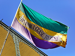 09 February 2016. New Orleans, Louisiana.<br /> Mardi Gras Day. A flag flutters in the breeze in the French Quarter. 'If ever I cease to love.'<br /> Photo©; Charlie Varley/varleypix.com