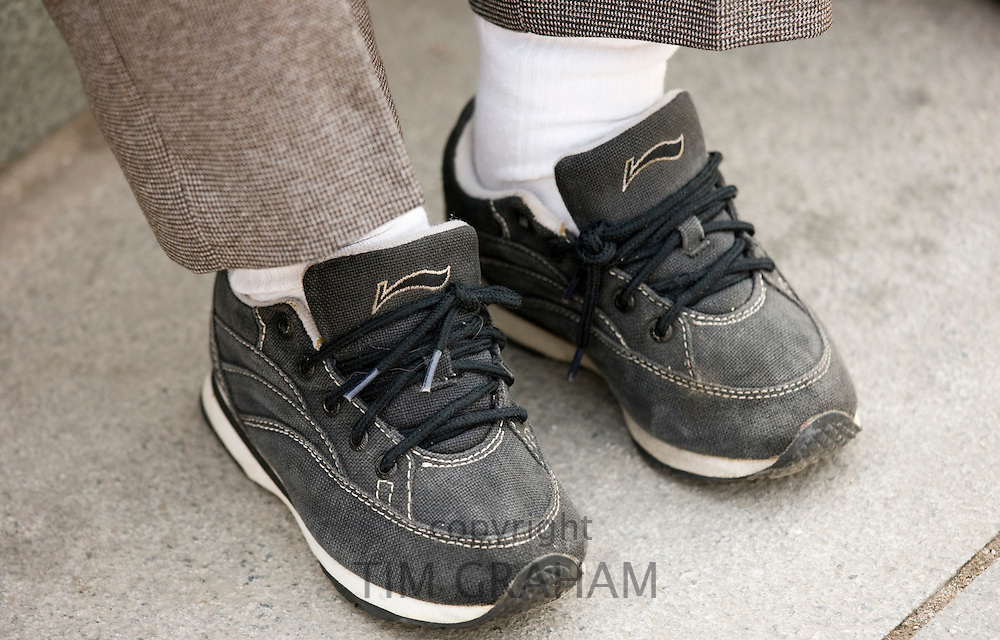 Elderly woman wears fake Nike trainers, her small feet having been previously bound, Xian, China