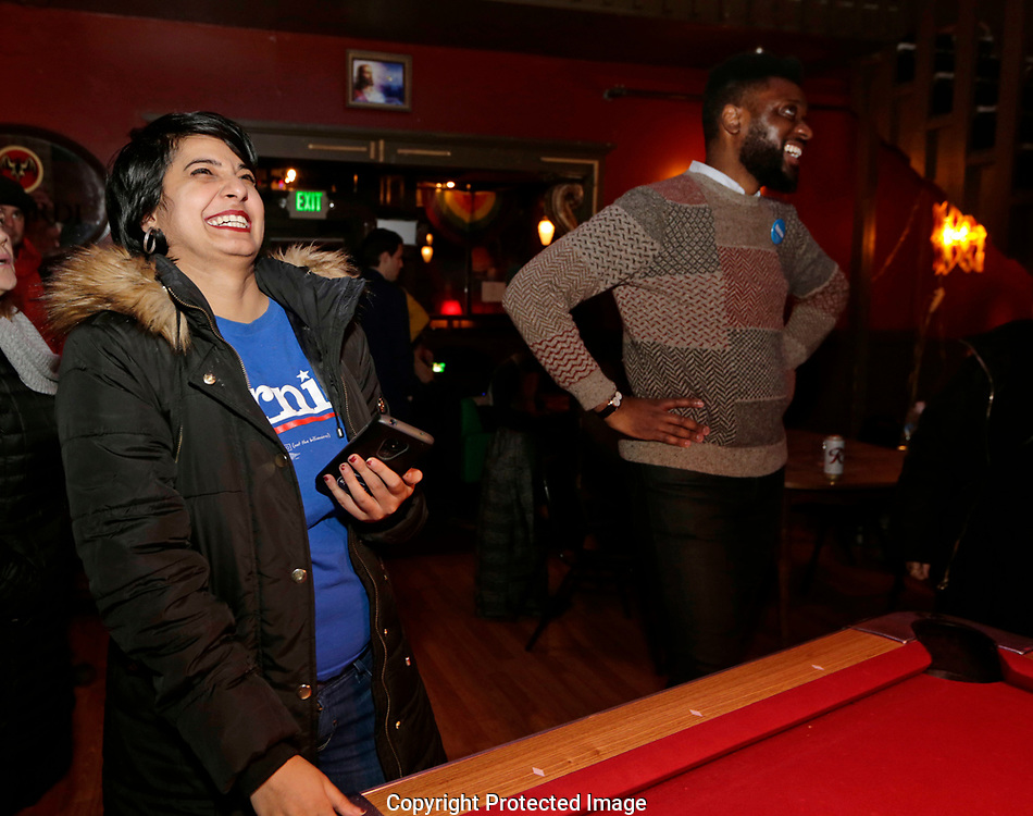 Supreep Kuar, left, and Shaun Scott, left, react to the first votes from King County at an informal campaign party for Democratic presidential candidate Sen. Bernie Sanders, I-Vt. as the first results come in for the Washington State primary, Tuesday, March 10, 2020, in Seattle. (AP Photo/John Froschauer)