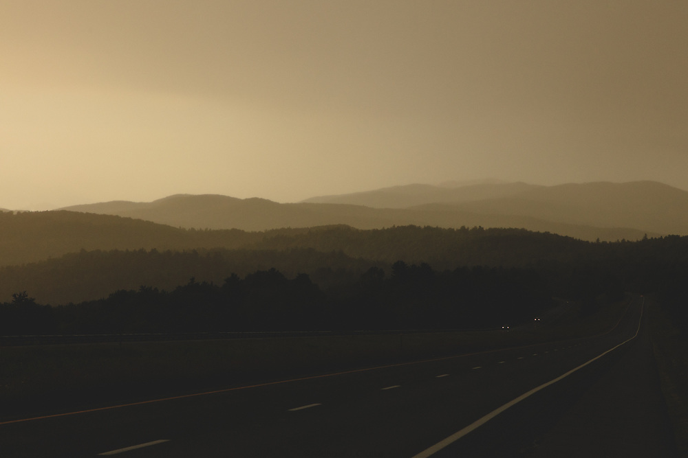 The highway leads an endless path along the hills of Vermont on a misty summer evening.