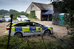 NOTE TO EDITORS : IMAGES SHOT FROM PUBLIC FOOTPATH © Licensed to London News Pictures. 11/08/2020. Bisley, UK. Police guard the entrance to Priest Lane Farm near Bisley in Surrey as investigators carry out an historic murder investigation. Surrey Police, supported by the British Army and specialist forensic teams are carrying out a dig in relation to the murder of Tina Baker, 41, in 2002. Tina was initially reported missing after last being seen in Sunbury on 8 July 2002 but the investigation became a murder enquiry in October 2002. In 2005, following an extensive investigation by the Surrey and Sussex Major Crime Team, Tina's husband, Martin Gerald Baker, was arrested and charged with her murder. In 2006, he was sentenced to 14 years behind bars. Tina's body was never recovered. Following the conviction, enquiries continued by Surrey Police in order to find out what happened to Tina Baker's body. Information received has resulted in the decision to carry out forensic investigations in Bisley. Photo credit: Peter Macdiarmid/LNP