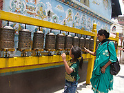 A women and child is runninmg their hands across prayer wheels making them spin. The prayer wheel all contain variuos prayers to Buddha and it is tradition to spin them to say prayers. Below and around the Boudhanath stupa, part of Nepal's four UNESCO World Heritage Sites. are numerous prayers wheels. The stupa is one of the most holy sites of pilgrimage for Buddhists around the world. Near Kahmandu, in the valley.