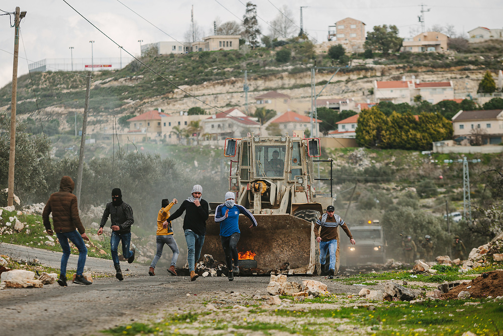 Palestinians throw stones and run away from an Israeli bulldozer during a weekly demonstration against the expropriation of Palestinian land by Israel and against the closure of the main road leading to Nablus, in the Palestinian village of Kufr Qaddum, West Bank, on February 21, 2020. The Israeli settlement of Kdumim, is seen in the background.