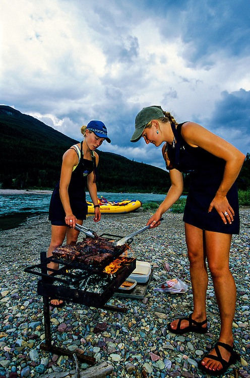 River guides cooking lunch on the shore, Whitewater rafting (with Glacier Raft Company), Flathead Valley, near West Glacier, Montana USA