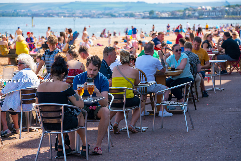 Edinburgh, Scotland, UK. 31 July, 2020. Temperature of 25C and sunshine brought huge crowds to Portobello Beach outside Edinburgh. Several large groups of teenagers were enjoying beach and alcoholic drinks were very popular.