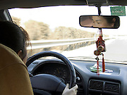 Asian woman driving while her eyes are seen in the rearview mirror China