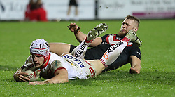 St Helens Saints' Theo Fages goes over for a try past London Broncos' Matthew Davies, during the Betfred Super League match at the Totally Wicked Stadium, St Helens.