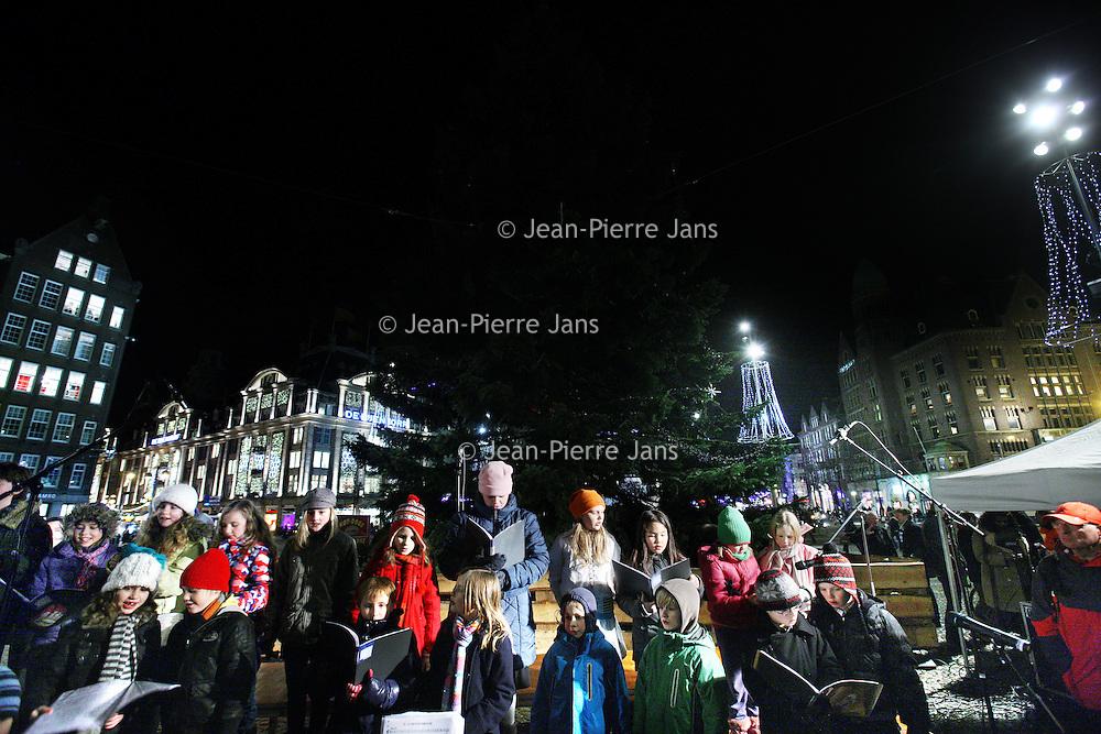Nederland, amsterdam , 9 december 2010..De Kerstboom op de Dam werd verlicht onder vele belangstellenden..Op de voorgrond een koortje bestaande uit kinderen die kerstliederen zongen.Chistmas tree on the Dam in Amsterdam, children choir singing chrismas carols.