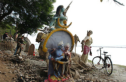 Relics from a  puja ceremony to Hindu Gods including Ganesh, the half human-half elephant God sit on the banks of a river in Tezpur, in Assam, eastern India December 25, 2003. India and its sacred elephants are threatened by deforestation and encroachment of the reserved land and natural forests.  As a result, wild elephants are rampaging through villages, killing people and destroying their homes and crops but still people revere the elephants. (Ami Vitale)