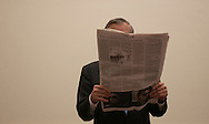 Secretary of Defense Donald H. Rumsfeld reviews the local paper prior to a NATO conference in Brussels, Belgium, on Dec 2, 2003.