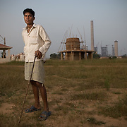 A cow herder stands in front of the half constructed temple at the resettlement colony at Jharsuguda. In the back are the chimneys of the industrial project that resettled the displaced population.