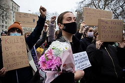 © Licensed to London News Pictures. 14/03/2021. London, UK. A woman holds flowers outside New Scotland Yard during a protest against the Police, Crime, Sentencing and Courts Bill 2021 that if passed will introduce new restrictions on protest. This demonstration comes after police arrested attendees at a vigil for Sarah Everard on Clapham Common last night.  Photo credit: George Cracknell Wright/LNP