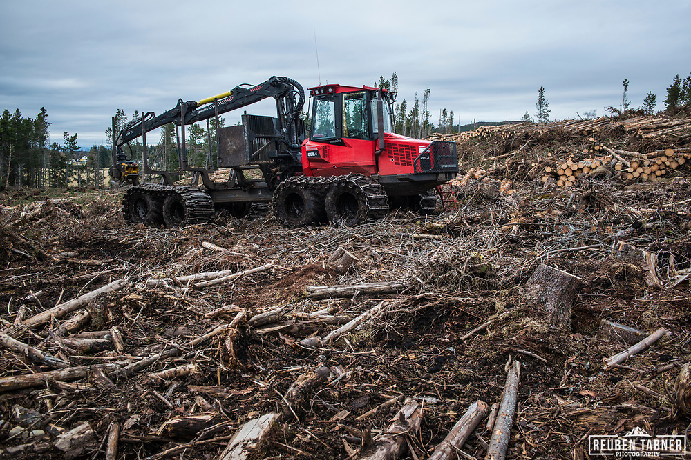 A red Komatsu 860.4 forest forwarder, parked in an area of clear fell, near Inverness in Scotland.