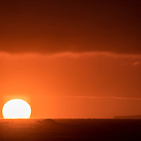 The sun appears as a bright orange ball as it fades below the horizon in the Southern Ocean off of Antarctica. A tabular iceberg can be seen in the distance.
