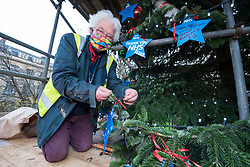 "© Licensed to London News Pictures; 17/11/2020; Bristol, UK. TONY MILES (a.k.a. Smiley Miley of Radio 1 Roadshow) holds stars to be placed on a giant Christmas tree for the ""Florence NHS Christmas Tree"" Thank You NHS Stars Fundraiser, with blue stars signed by among others the UK Prime Minister Boris Johnson, Health Secretary Matt Hancock and Deputy Chief Medical Officer Jonathan Van-Tam. For the 10th year Clifton Village in Bristol has a 50ft illuminated Christmas tree, the tallest in any UK village. Photo credit: Simon Chapman/LNP."
