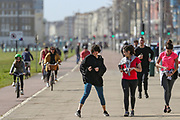 April 6, 2020, London, England, United Kingdom: Girls dancing as they walk beside the Brighton beach at midday in Brighton, East Sussex, as the country is in lockdown to help curb the spread of the coronavirus, Monday, April 6, 2020. (Credit Image: © Vedat Xhymshiti/ZUMA Wire)