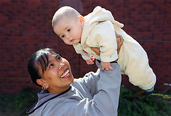 Mother holding baby son in the air smiling,