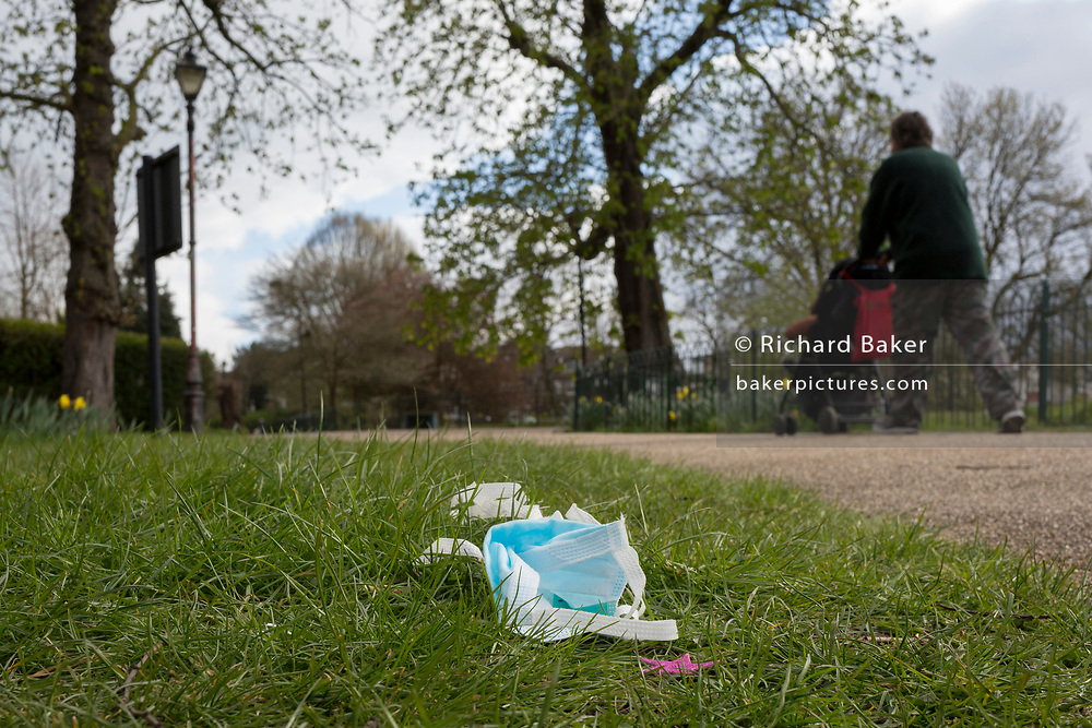 At the beginning of the second week of the UK's Coronavirus lockdown and in accordance with government guidelines for social distancing and local daily exercise, a used discaded surgical mask lies in the grass alongside a passing father and child in Ruskin Park, a green public space in the borough of Lambeth, south London, on 30th March 2020, in London.