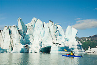 "A kayaker checks out a ""kryptonite"" iceberg on Bear Lake, Kenai Fjords National Park, Alaska"