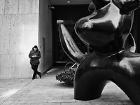 """Texting under the watchful eye of Joan Miro's """"Moonbird"""" sculpture at the Solow Building on 58th Street , New York"""