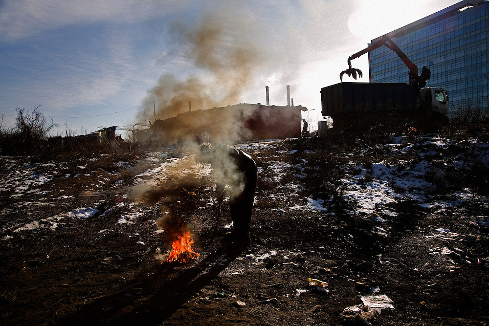Roma living in the Belville camp in New Belgrade. Truck takes away scrap metal for processing and man burns electrical wire to recover valuable metal to recycle.