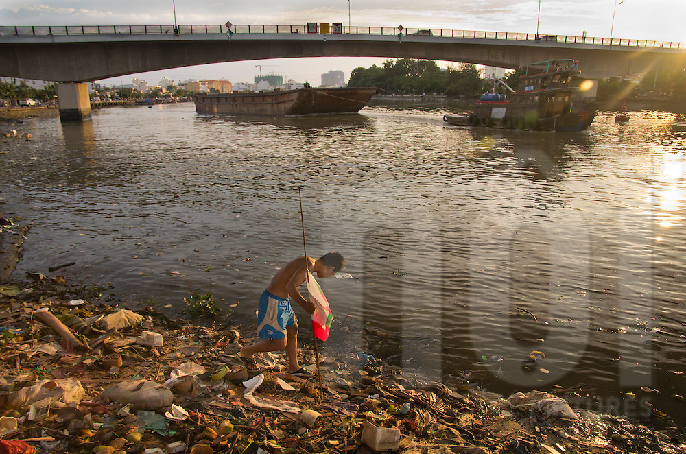Life along the river in Ho Chi Minh city, Vietnam, Asia. A man looking for what is recoverable from the garbage