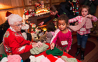 Nana Hamel helps Dulce and Ella pick out a Christmas scarf during their visit to Christmas Village on opening night Thursday evening.  (Karen Bobotas/for the Laconia Daily Sun)