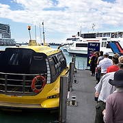 Passengers board a water taxi at The Ferry Terminal at Auckland Harbour, showing the Hilton Hotel in the background. Auckland, New Zealand, 31st Ovtober 2010. Photo Tim Clayton.