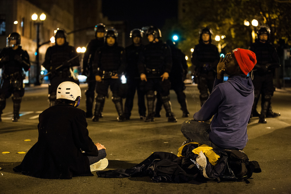 OAKLAND, CA - NOVEMBER 14, 2011: An Occupy Oakland protester calls out to his friends after joining another protester who took it upon himself to confront a line of Oakland Police officers.