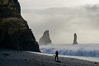 Photographer at Reynisfjara black sand beach. Waves crashing on beach, Reynisdrangar Sea Stacks in background. South Coast of Iceland.