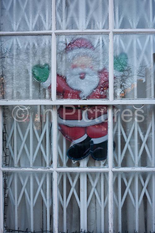 A detail of a Santa sticker displayed in a security window of a vacant East End home, on 2nd January 2017, London, England.