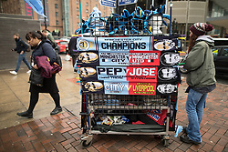 © Licensed to London News Pictures. 07/04/2018. Manchester, UK. A street peddler selling half and half , two team , scarves with graphics of Pep Guardiola and Jose Mourinho featured , in Piccadilly in Manchester , ahead of the Manchester City vs Manchester United derby match. If they win the match, Manchester City will win the League title. Photo credit: Joel Goodman/LNP