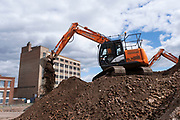 Diggers work on moving a huge pile of bricks as part of a development / redevelopment of old industrial builindgs in the city centre on 28th July 2020 in Birmingham, United Kingdom. The city is under a long term and major redevelopment, with much of its industrial past being demolished and made into new flats for residential homes, as part of the Big City Plan.